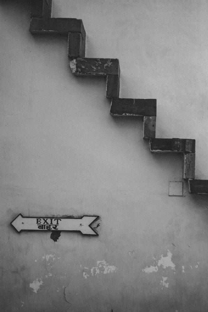 Auf dem schwarz-weiß Foto ist eine Hauswand. Von der rechten mittleren Seite des Bildes führt nach oben in die linke Ecke eine Treppe. Im unteren linken Viertel des Bildes befindet sich ein Pfeil mit der Aufschrift Exit.