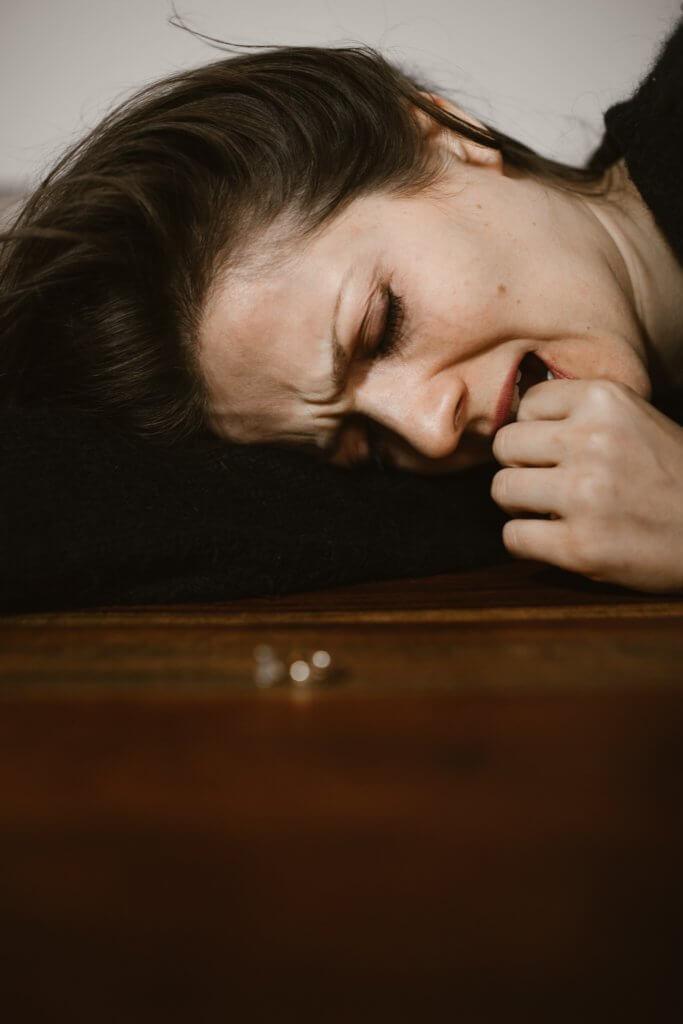 Eine verzweifelte, weinende Frau liegend vor einem Ring. Nur ihr Kopf ist sichtbar.