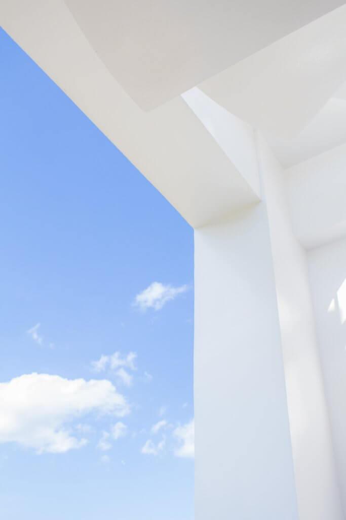 Blick auf einen strahlend blauen Himmel mit vereinzelten Kumulus Wolken. Der Himmel wird auf der rechten und oberen Seite des Bildes durch weißes Mauerwerk begrenzt. So entsteht der Eindruck, dass Du aus einem Haus hinaus in den Himmel schaust.